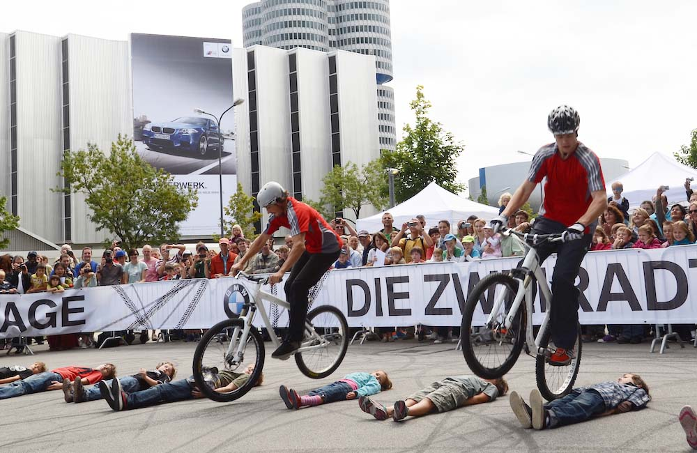 dual-bike-trial-show-fahrer-springen-ueber-menschen-am-boden