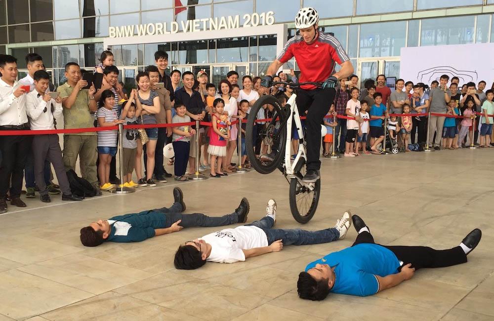 bike-trial-show-fahrer-springt-ueber-am-boden-liegende-personen