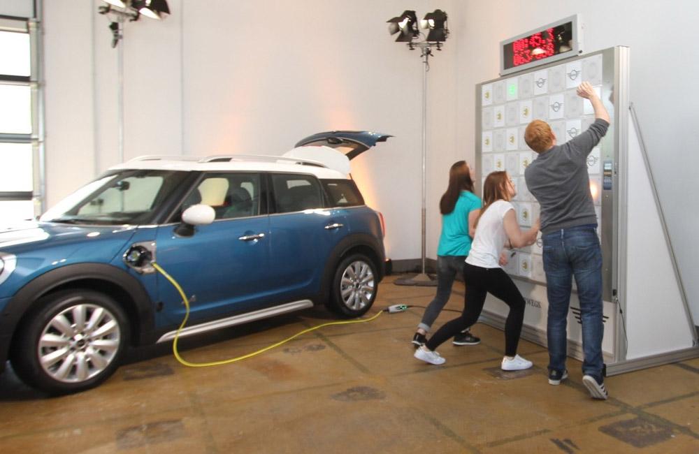 2-kinder-und-mann-spielen-an-touch-wall-und-laden-ein-elektroauto-auf