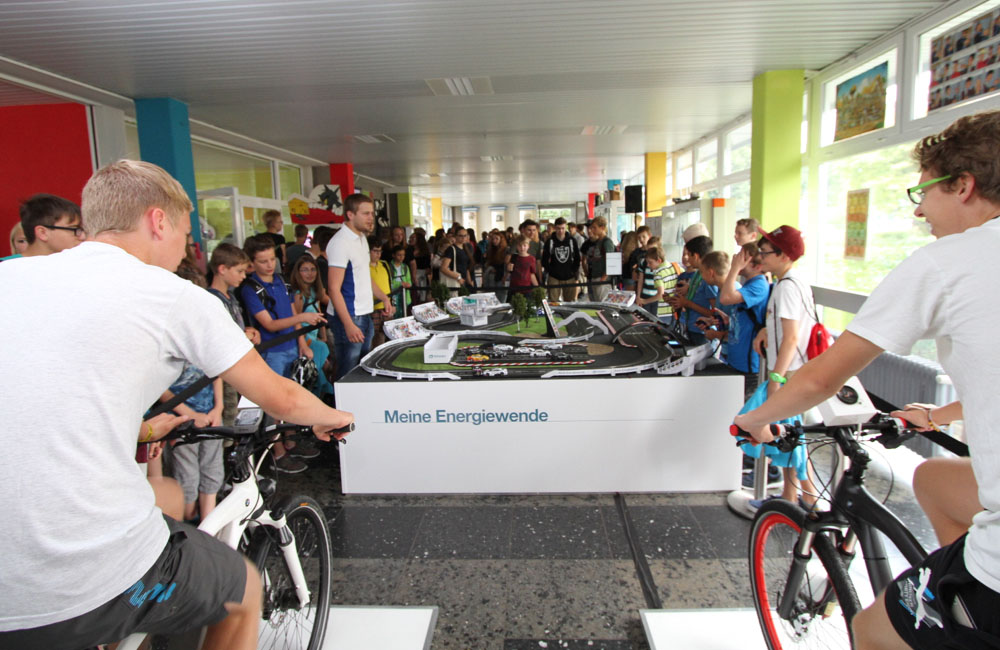 carrerabahn-mit-zuschauern-und-zwei-jungen-auf-bike-simulatoren