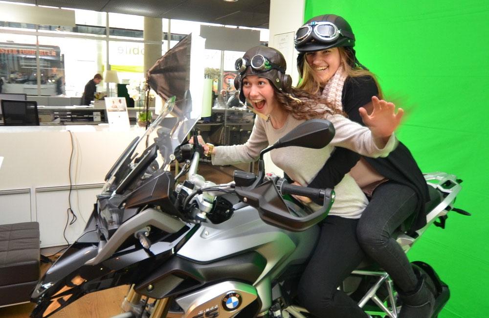zwei-maedchen-sitzen-auf-einem-motorrad-vor-dem-greenscreen
