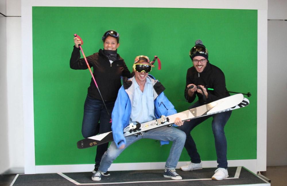 drei-menschen-posieren-vor-greenscreen-mit-skiequipment